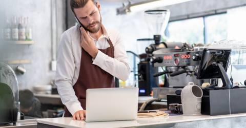 Serieuze bezorgde man wat een telefoongesprek voert en tussendoor naar informatie op zijn laptop aan het kijken is in een koffiebar
